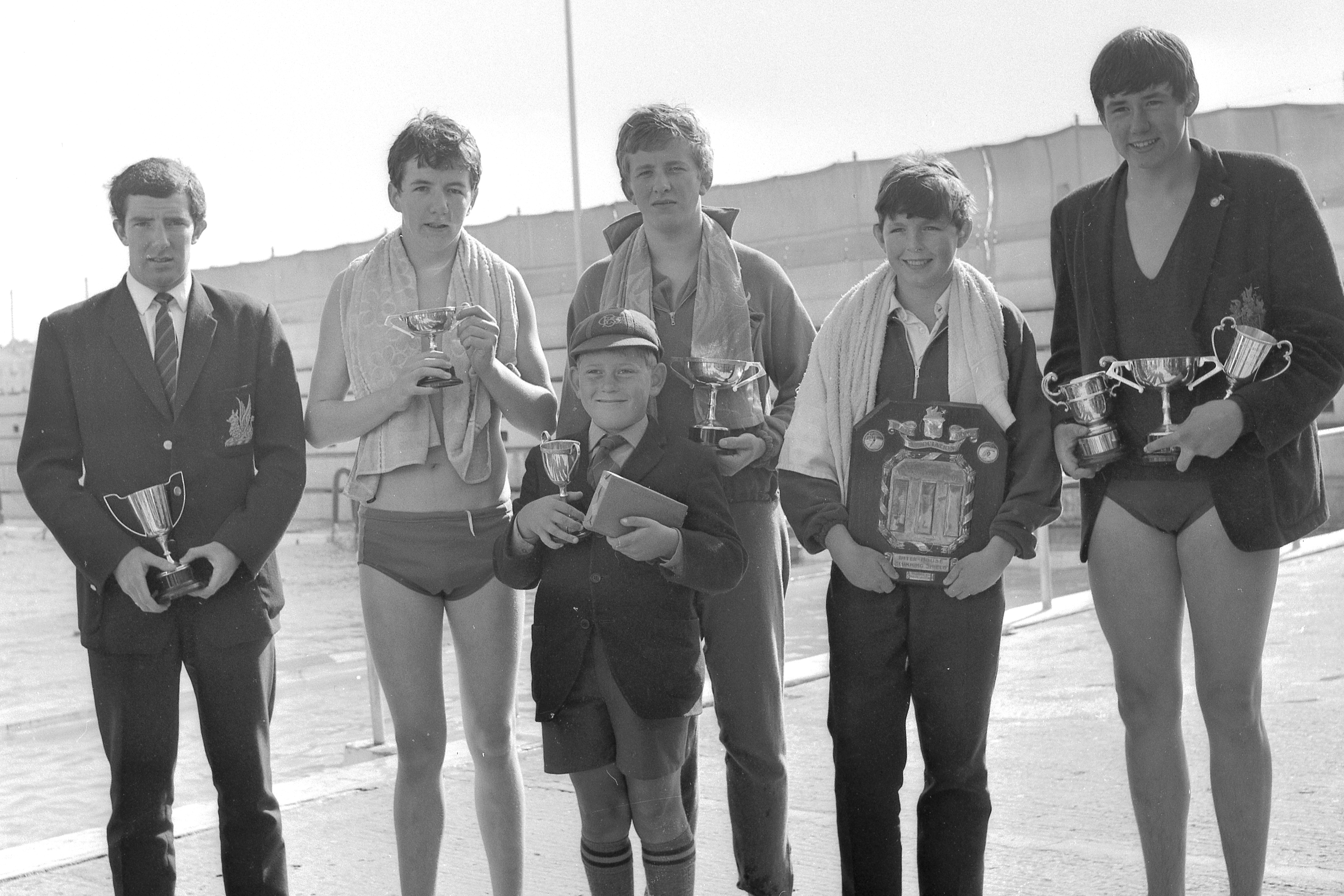 One of the few surviving photographs - taken by the County Down Spectator at the 1966 Gala - that features all the cups awarded for swimming. From left: W. R. Rowley (Breaststroke Cup); W. D. McKeown (Jamison Cup - Freestyle); R. H. Thompson (Jamison Cup - Freestyle, Connor House); R. A. Anderson (Diving Cup); D. Eadie (House Shield); and R. Whyte (Sir Walter Smiles Cup for top swimmer at the Gala, Butterfly Backstroke Cup and  Butterfly Cup).